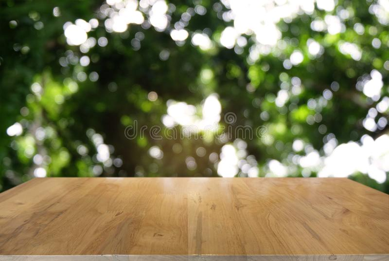 Image of dark wooden table in front of abstract blurred background of outdoor garden lights. can be used for display or montage y stock photo