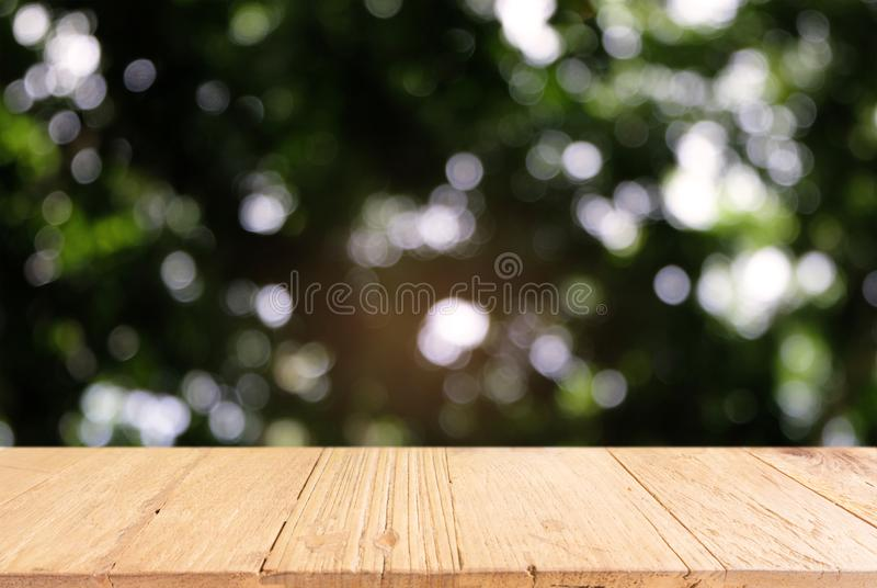 Image of dark wooden table in front of abstract blurred background of outdoor garden lights. can be used for display or montage y royalty free stock image