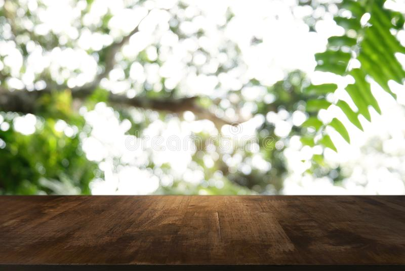 Image of dark wooden table in front of abstract blurred background of outdoor garden lights. can be used for display or montage y royalty free stock images