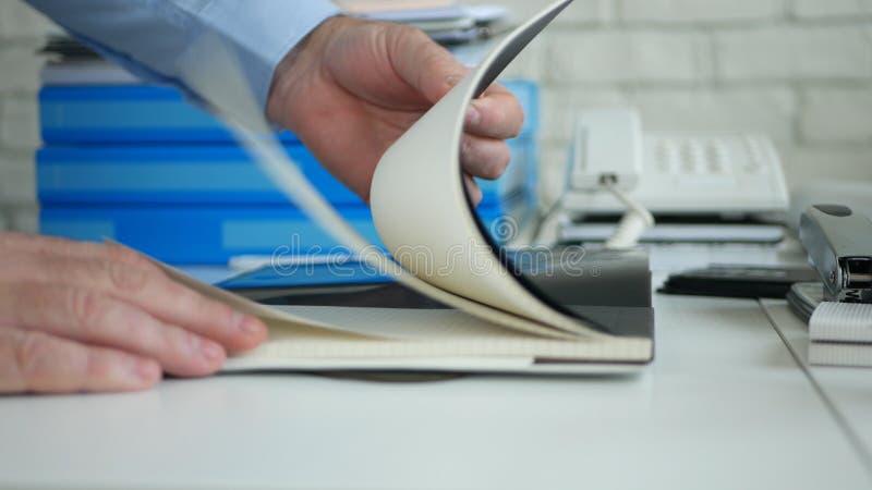 Image de bureau avec des pages d'ordre du jour et de lecture rapide de Hands Opening New d'homme d'affaires image stock