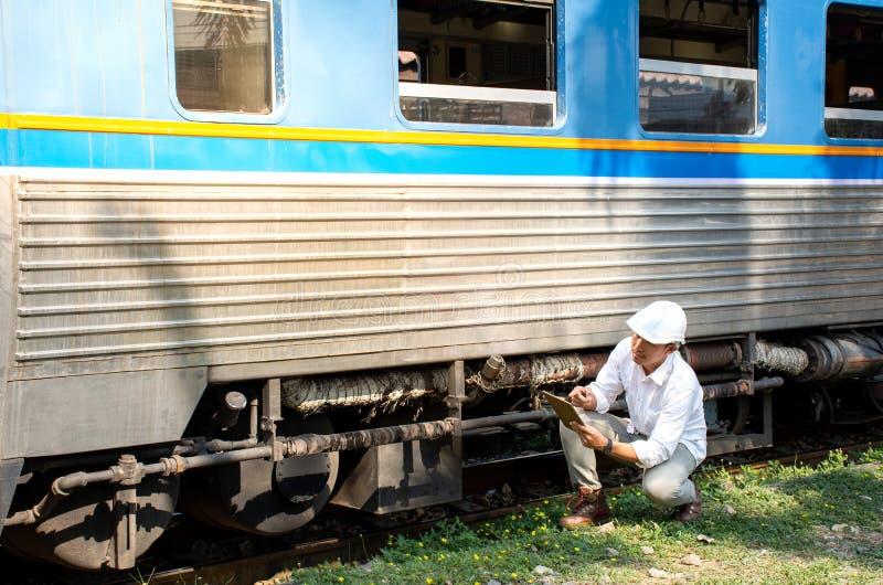 Image de casque de sécurité de port d'ingénieur asiatique avec examiner le train pour assurer l'entretien dans la station photos stock