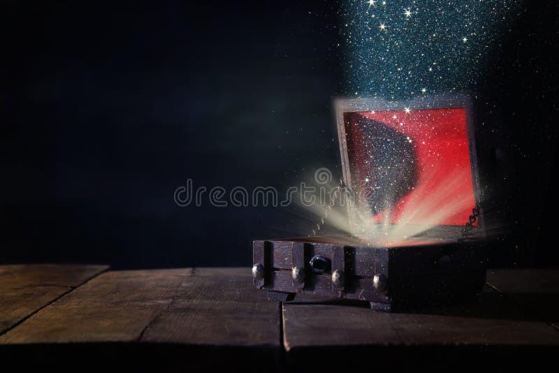 Image de coffre au trésor mystérieux avec la lumière de scintillement et de fumée au-dessus de vieux livre sur la table en bois image stock