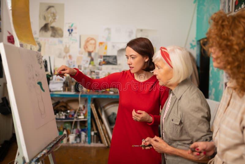 Image de coloration d'étudiant en art près de professeur et d'ami photo libre de droits