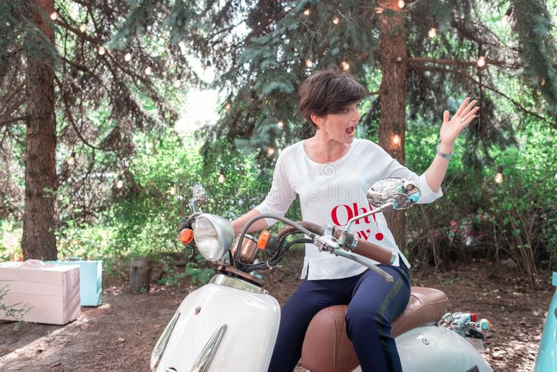 Image de cru de jeune femme attirante sur le vieux rétro scooter photos libres de droits