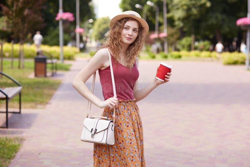 Image de dame sincère sincère attirante avec les cheveux bouclés se tenant au milieu du parc local vert, ayant la promenade, s'ar image libre de droits