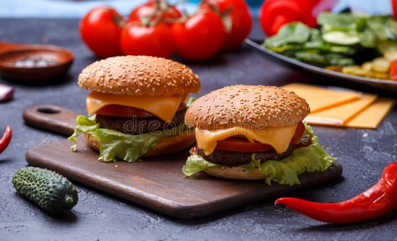 Image de deux hamburgers sur le panneau en bois, fromage photographie stock