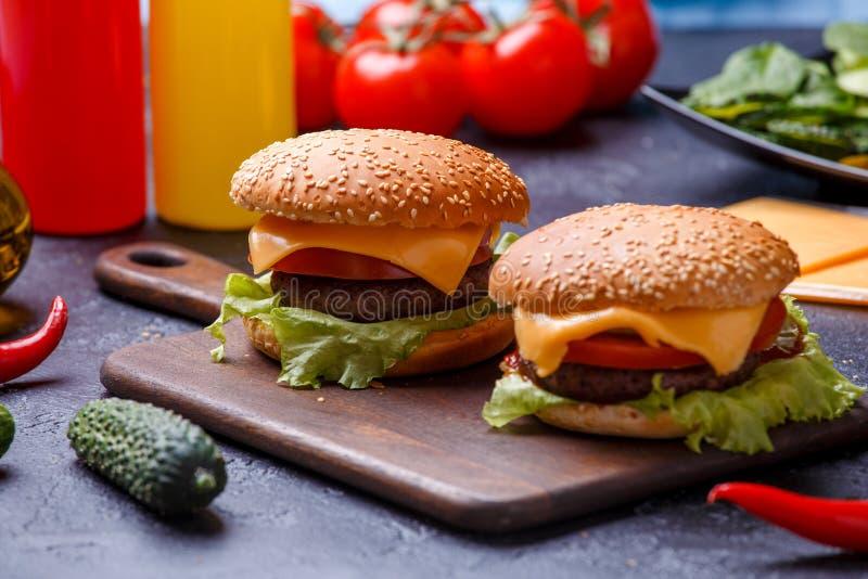 Image de deux hamburgers sur le panneau en bois, fromage photos libres de droits
