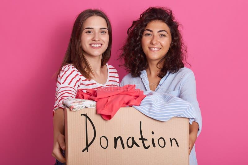 Image de deux jolies filles de brune utilisant les chemises rayées et bleues rouges, présentant la boîte avec les vêtements vifs  image stock