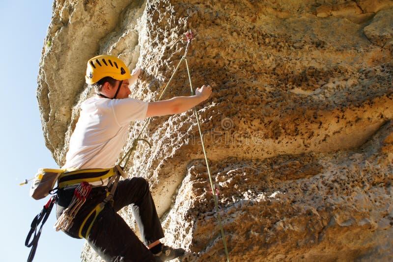 Image de dos d'homme de touristes du ` s dans le casque et le T-shirt blanc escaladant la montagne pour compléter image libre de droits