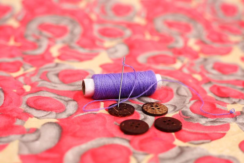 Image de fil, d'aiguille et de bouton quatre pourpres de couture photographie stock