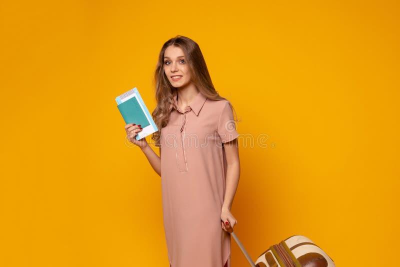 Image de fille heureuse de sourire avec de longs cheveux dans la robe beige d'été tenant les billets de vol et la valise image stock