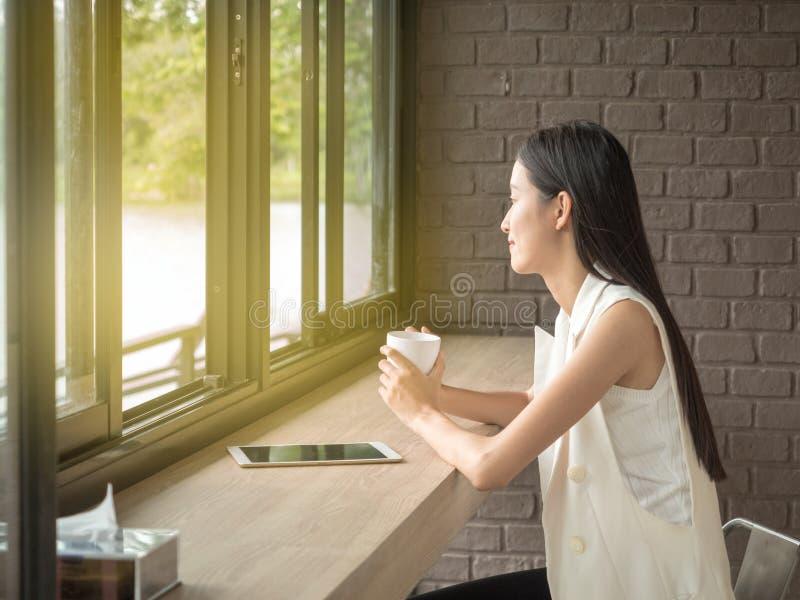 Image de jeune et jolie femme de l'Asie avec la tasse de café et de regarder la fenêtre photographie stock