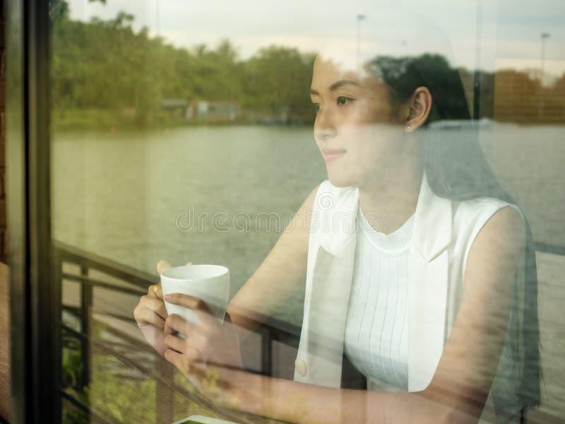 Image de jeune et jolie femme de l'Asie avec la tasse de café et de regarder la fenêtre photo stock