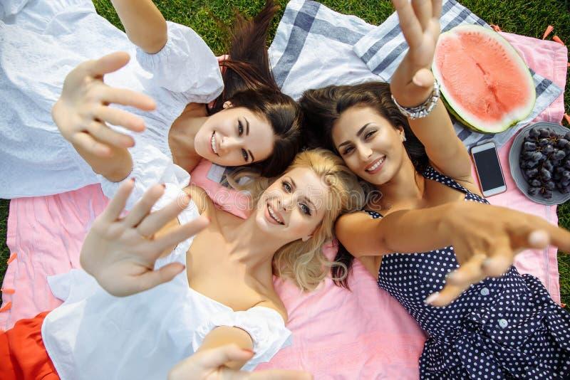 Image de jeunes femmes attirantes de sourire se trouvant sur l'herbe verte et montrant des paumes image libre de droits