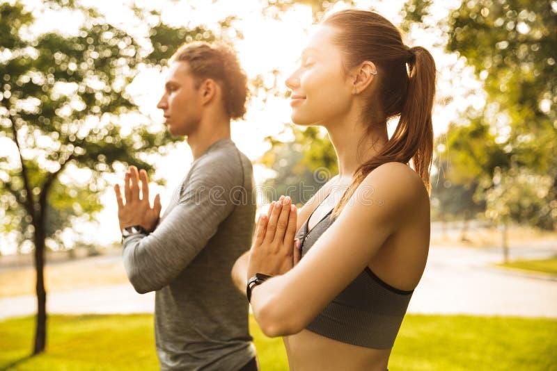 Image de l'homme de couples et de la femme sportifs sportifs 20s dans les survêtements, images libres de droits