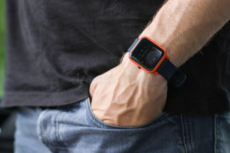 Image de l'homme mettant sa main dans sa poche de pantalon de jeans, utilisant une montre intelligente technologie Arbres sur le  image stock