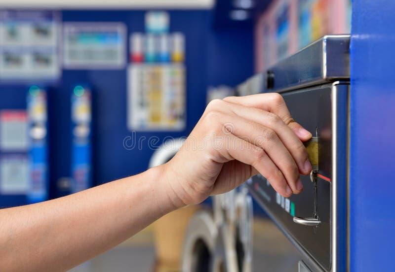 Image de l'insertion manuelle de pièces dans la laverie en libre-service photographie stock