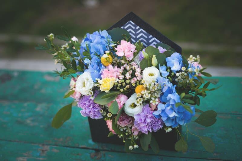 Image de la belle disposition de fleurs avec l'hortensia bleu, eustoma blanc, roses de jet, oeillets sur la table en bois image libre de droits