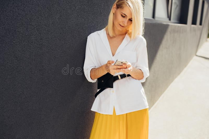 Image de la belle jeune lecture femelle caucasienne ou message textuel textotant au téléphone portable posant sur le mur gris ext photo stock