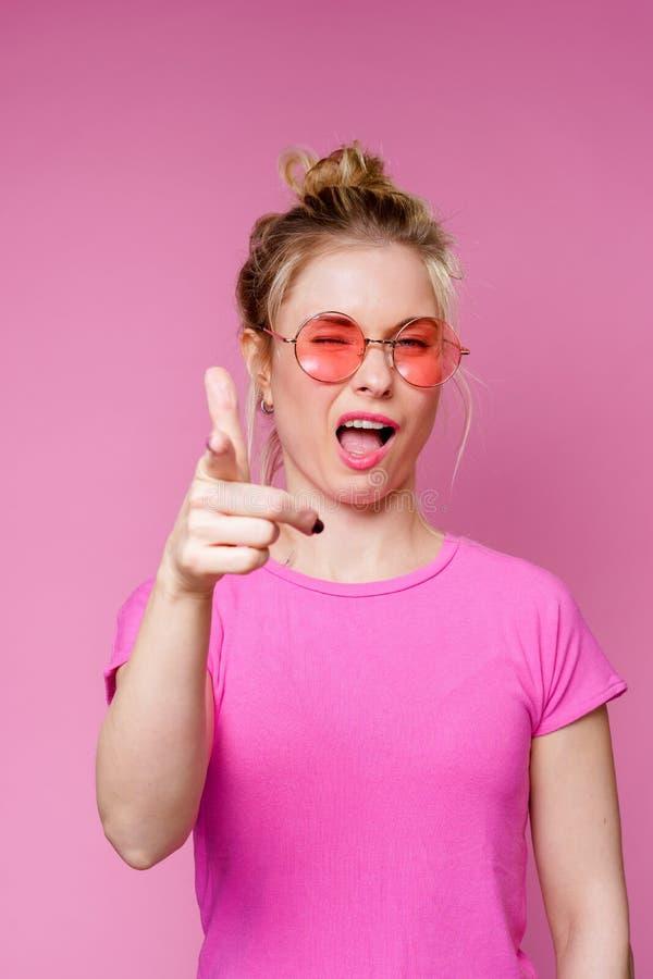 Image de la blonde de sourire en verres roses dirigeant le doigt en avant photos libres de droits