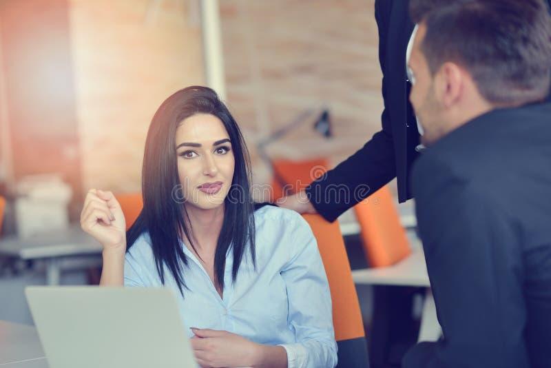 Image de la femme à l'aide de l'ordinateur portable tout en se reposant à son bureau photo stock