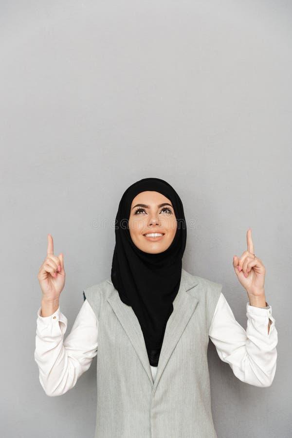 Image de la femme arabe 20s dans le hijab souriant et semblant les WI ascendants photo stock