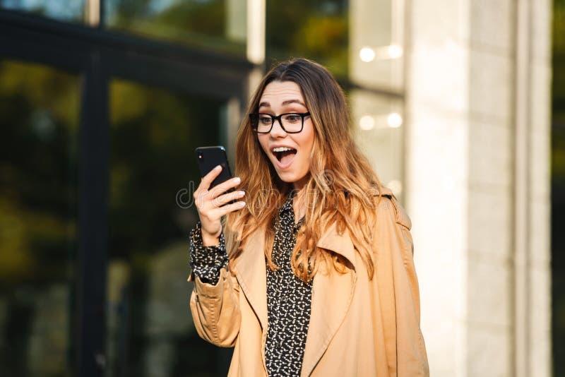 Image de la femme enthousiaste à l'aide du téléphone portable tout en marchant par la rue de ville images stock