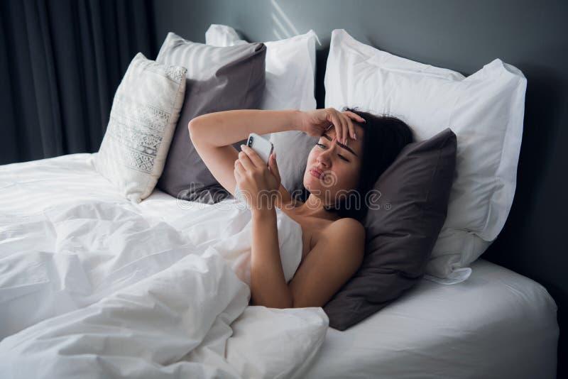 Image de la femme frustrante 20s de renversement avec les cheveux foncés se situant dans le lit sur l'oreiller blanc après sommei photo stock