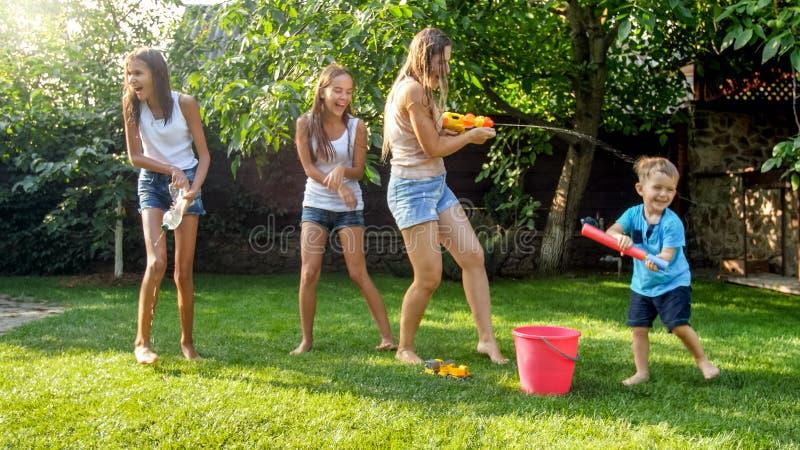 Image de la jeune m?re de wuth gai heureux d'enfants jouant avec les armes ? feu d'eau et la maison de jardin Famille jouant et a photos libres de droits