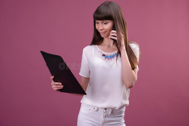 Image de la jeune position de femme d'affaires au-dessus du fond rose regardant de c?t? causant par le dossier de participation d photos libres de droits