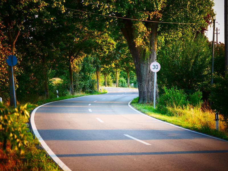 Image de la limitation de vitesse du kmh 30 à côté d'une route sinueuse photos stock