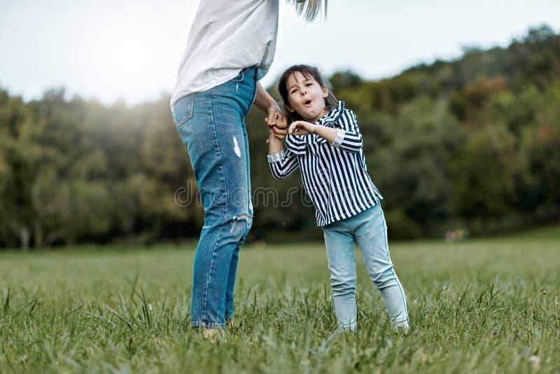 Image de la petite fille heureuse mignonne jouant avec sa belle mère dehors en parc Temps heureux de famille ensemble positif image libre de droits