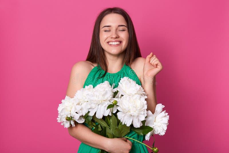 Image de la pose positive belle de modèle d'isolement au-dessus du fond rose dans le studio, fermant ses yeux, soulevant une main images libres de droits