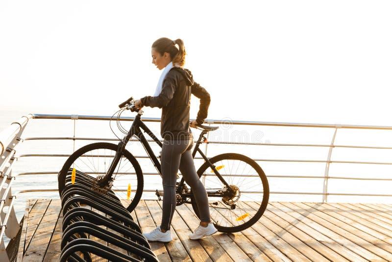 Image de la position de femme de forme physique avec la bicyclette sur la promenade, pendant le lever de soleil au-dessus du fond photos stock