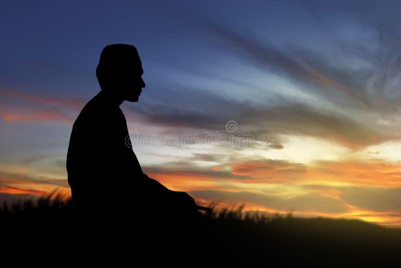 Image de la prière d'homme de silhouette photos stock