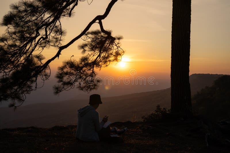 Image de lever de soleil ou de coucher du soleil sur l'horizon orange et jaune avec la silhouette de personnes entourée par des p photographie stock