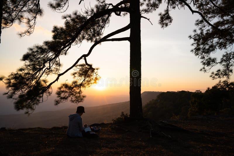 Image de lever de soleil ou de coucher du soleil sur l'horizon orange et jaune avec la silhouette de personnes entourée par des p images libres de droits