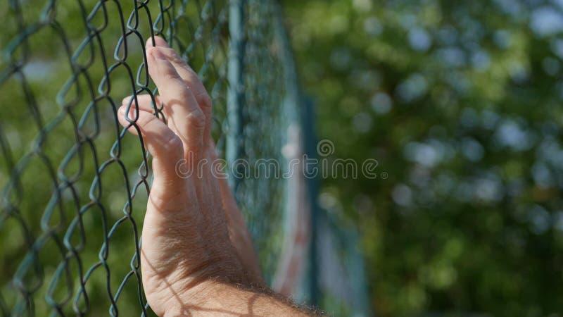 Image de mains d'homme accrochant dans une barrière métallique images stock
