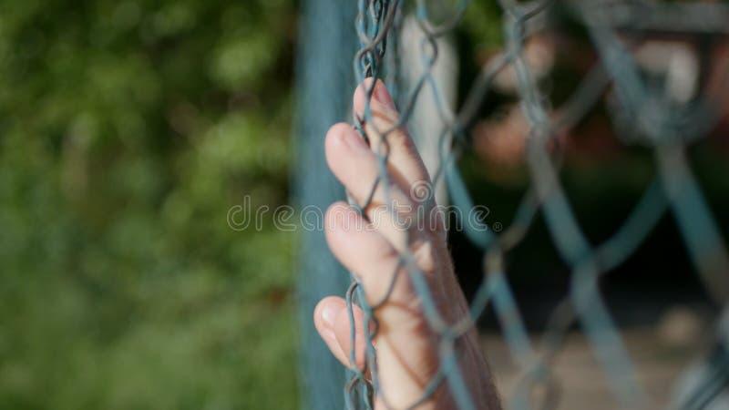 Image de mains d'homme glissant sur une barrière métallique photo libre de droits