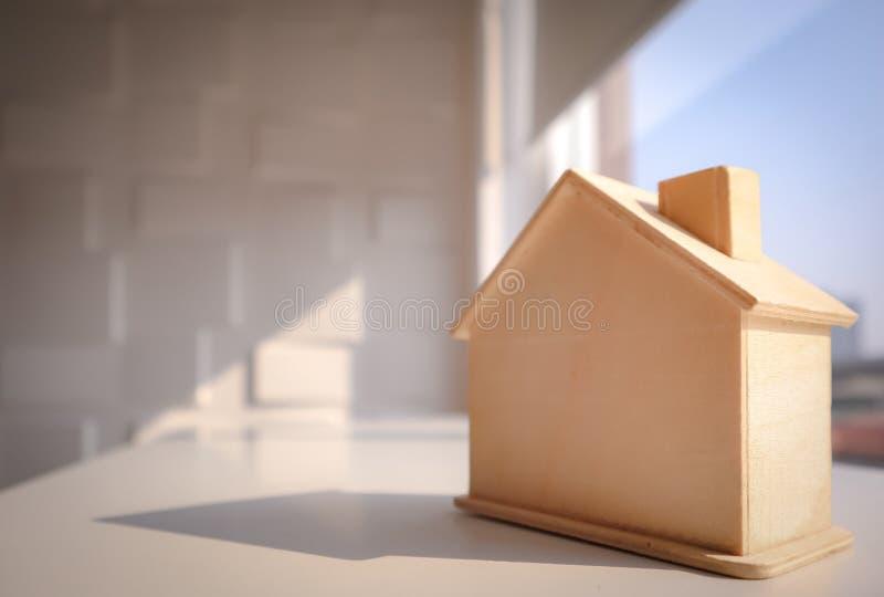 Image de maison modèle en bois brun clair sur la table avec le fond du paysage urbain et du ciel photos stock
