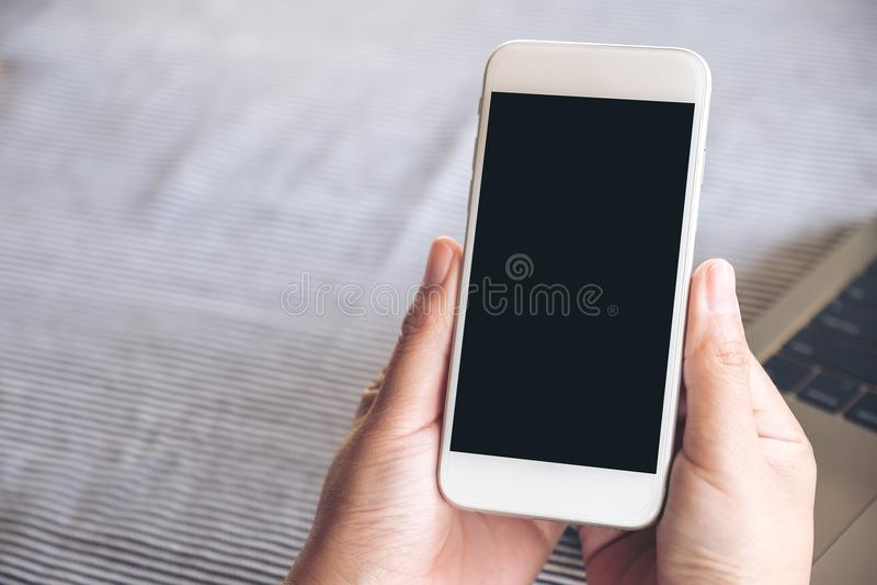 Image de maquette des mains tenant le téléphone portable blanc avec l'écran et l'ordinateur portable de bureau noirs vides photos libres de droits