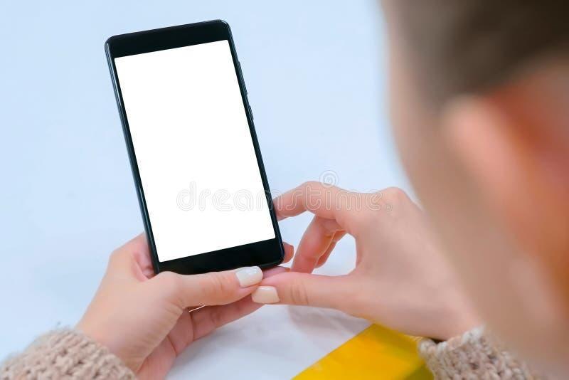 Image de maquette - femme tenant le smartphone noir avec l'écran vide blanc photo stock