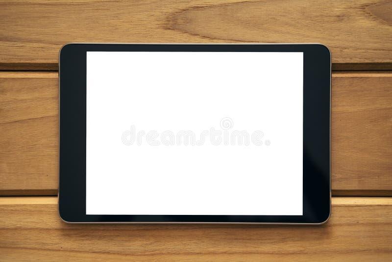 Image de maquette de fin vers le haut de PC noir de comprimé avec l'écran blanc vide sur la table en bois de vintage photo libre de droits