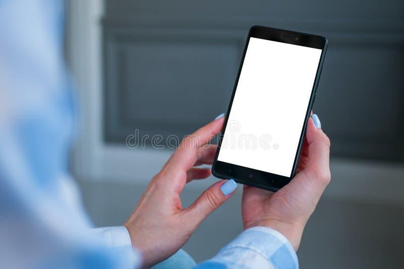 Image de maquette de smartphone avec l'écran vide blanc chez des mains de la femme image stock