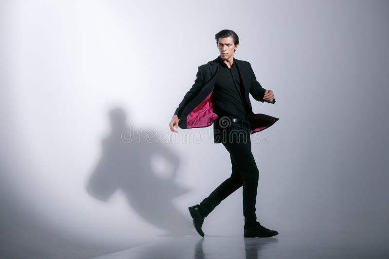 Image de mouvement d'un jeune homme fort attirant dans le plein costume noir élégant, d'isolement sur un fond blanc photo libre de droits