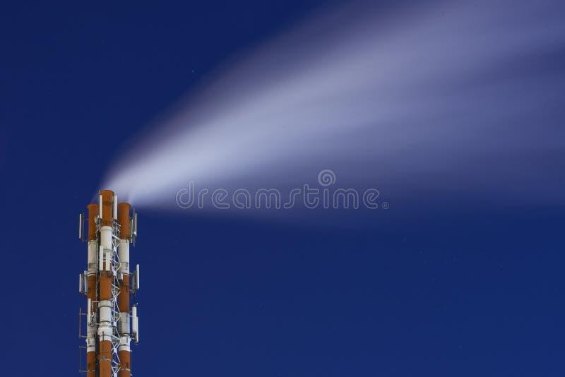 Image de nuit d'une tuyauterie de vapeur de système de tabagisme de cheminée d'usine contre un ciel étoilé foncé Industriel abstr photos libres de droits