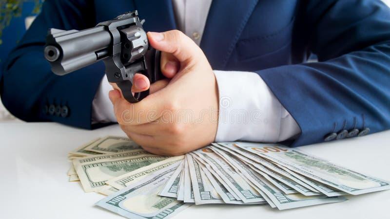 Image de plan rapproché d'homme d'affaires dans le costume protégeant son argent et visant avec le pistolet photo libre de droits
