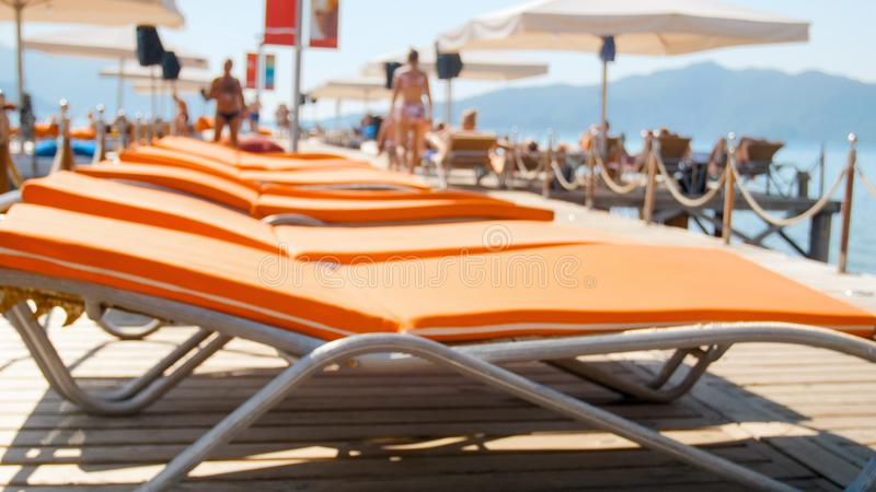 Image de plan rapproché des lits pliants vides sur la jetée en bois à la plage de mer photos stock