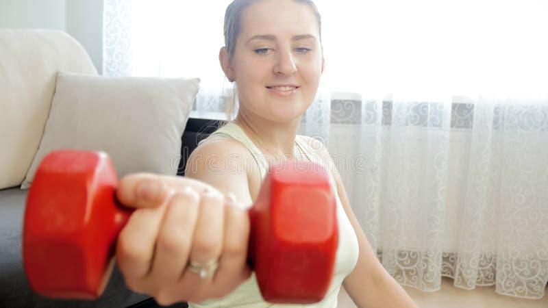 Image de plan rapproché de jeune femme se reposant sur le plancher et tenant l'haltère rouge photo stock