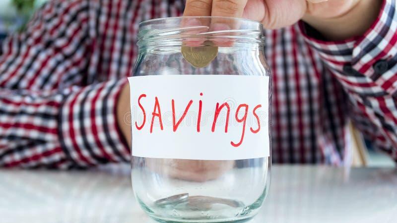 Image de plan rapproché de jeune homme mettant la pièce de monnaie d'or dans le pot en verre pour l'épargne d'argent images stock